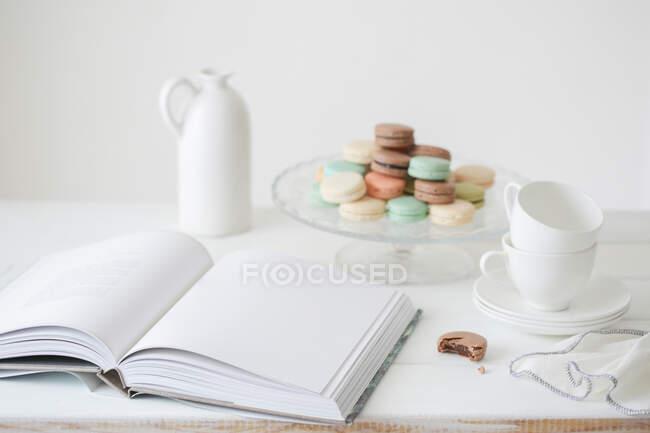 Сверху открытая книга с чистым белым листом на столе с тарелкой с красочными макаронами и чайным сервизом у белой стены — стоковое фото