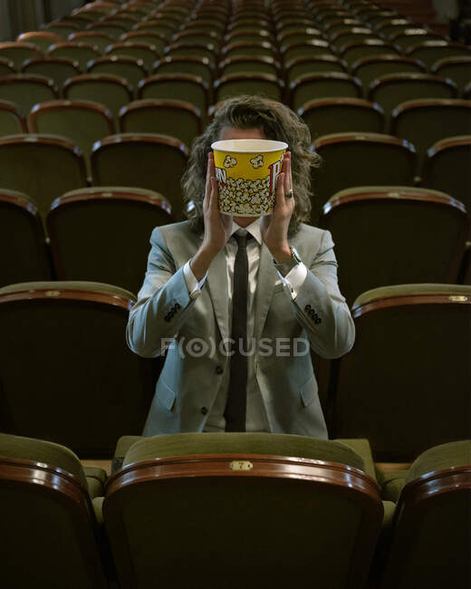 Unrecognizable man covering face with bucket of popcorn watching awful show in empty hall of theater — Stock Photo