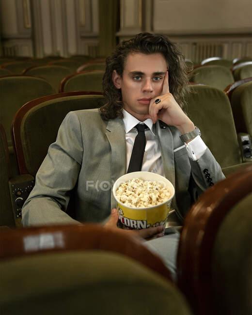 Jeune homme ennuyé avec seau de maïs soufflé regarder horrible spectacle dans le hall vide du théâtre en regardant la caméra — Photo de stock