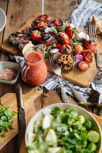 Dall'alto di deliziose verdure alla griglia aromatiche tra cui pomodori rossi e pepe con melanzane affettate e cipolla servita su tavola di legno su tavolo rustico con piatti fatti in casa — Foto stock