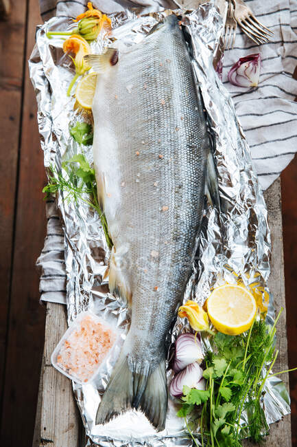 From above of fresh uncooked salmon fish seasoned with aromatic spices and herbs with lemon slices placed on aluminum foil on wooden table - foto de stock