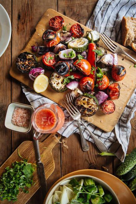 Desde arriba de verduras a la parrilla deliciosas aromáticas incluyendo tomates rojos y pimienta con berenjenas en rodajas y cebolla servida sobre tabla de madera sobre mesa rústica con platos caseros - foto de stock