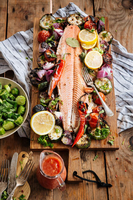 From above of delicious grilled salmon fillet garnished with assorted grilled vegetables served on wooden board on table with tomato sauce and bowl with salad — Stock Photo