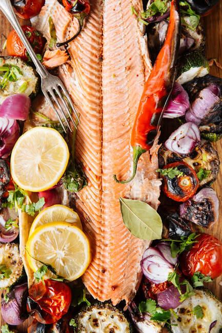 Desde arriba de delicioso filete de salmón a la parrilla adornado con verduras a la parrilla surtidos servidos en tablero de madera en la mesa con salsa de tomate y tazón con ensalada - foto de stock