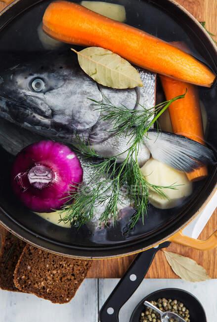 Верхний вид сырой рыбы и лука, помещенных в воду внутри кастрюли с морковью и картофелем дополненный укропом и лавровым листом во время приготовления супа — стоковое фото