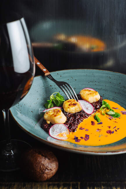 From above of appetizing haute cuisine delicacy served in ceramic plate with glass of red wine — Stock Photo