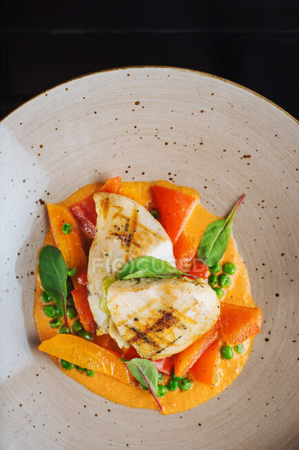 Top view of haute cuisine restaurant dish made with grilled fish and stew vegetables garnished with fresh spinach — Foto stock