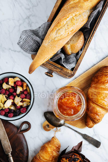 Top view composition of fresh baguette and croissants served with aromatic sweet apricot jam on marble table — стоковое фото
