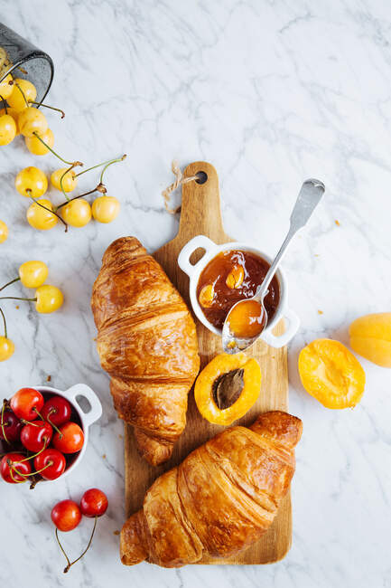 Top view of appetizing fresh croissant served with pot of homemade apricot jam on wooden cutting board placed near fresh fruits on marble background — Stock Photo