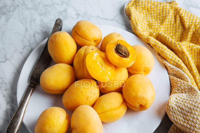 Top view of white plate with fresh yellow ripe apricots placed on yellow cloth on white marble table with cut in half apricot — Foto stock