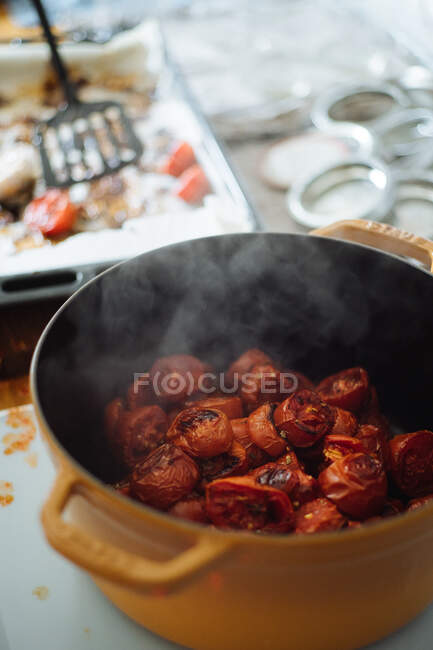 Hot pan with cooked tomatoes while preparing delicious sauce in kitchen - foto de stock