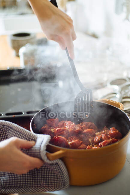 Crop unrecognizable housewife with spatula holding hot pan with cooked tomatoes while preparing delicious sauce in kitchen — Stock Photo