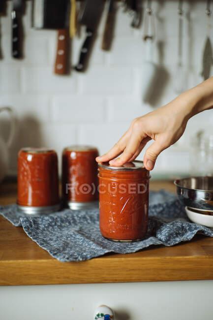 Cortar dona de casa colocando tampa no frasco de vidro com molho de tomate acabado de fazer enquanto prepara conservas caseiras na cozinha — Fotografia de Stock
