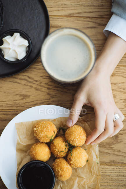 From above crop woman taking tasty potato croquette from plate while sitting at wooden table with hot drink — Stock Photo