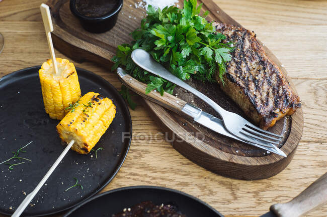 From above of delicious grilled steak served with fresh green herbs and grilled corn on sticks on wooden table — Stock Photo