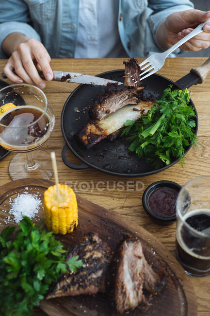 Crop unrecognizable person with knife and fork eating delicious grilled beef steak with bone served with fresh greenery and grilled corn in restaurant — Stock Photo