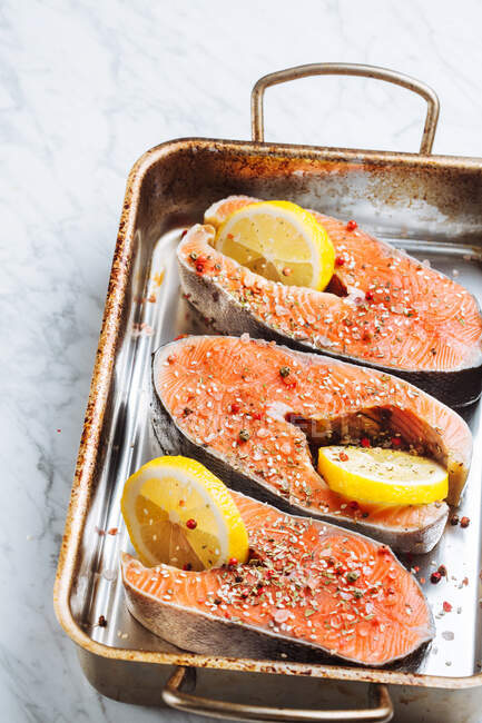Top view of fresh salmon steaks with aromatic seasoning and lemon slices placed on metal baking sheet — Foto stock