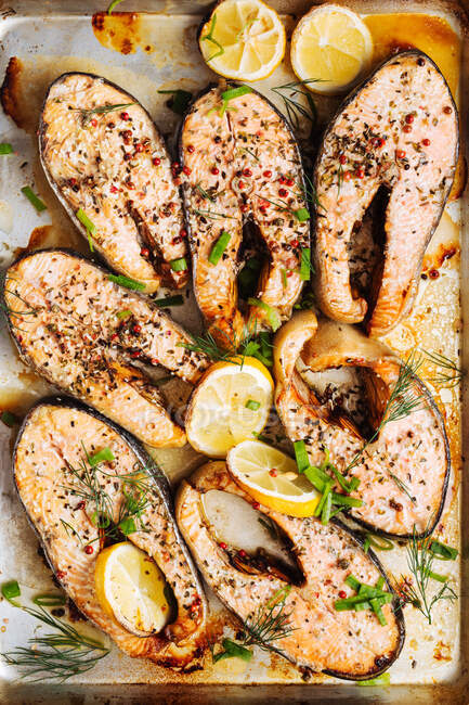Vista superior de deliciosos filetes de salmón asados con hierbas aromáticas y especias decoradas con rodajas de limón en bandeja para hornear de metal - foto de stock