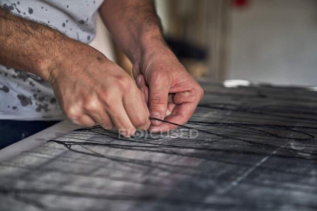 Crop artista masculino poniendo hilos negros en la lona mientras crea obras de arte en el estudio de artesanía - foto de stock