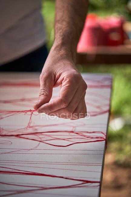 Hombre artesano trabajando con hilos en taller - foto de stock