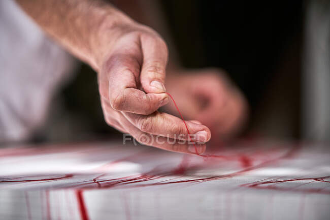 Male artisan working with threads in workshop — Stock Photo