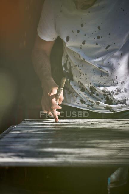 Crop hombre creativo en camiseta blanca con manchas negras de pie y apoyado sobre lienzo mientras se trabaja en la imagen en el taller - foto de stock