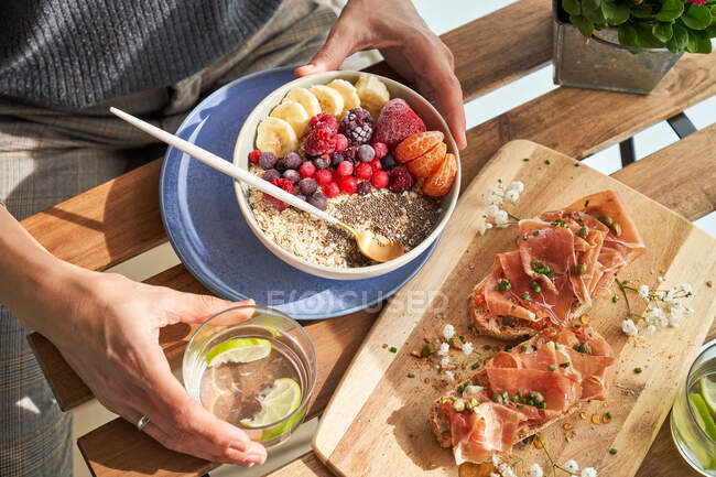 From above of faceless man eating fresh cereals with colorful berries at table with smoked red meat and glass of water with lime — Stock Photo