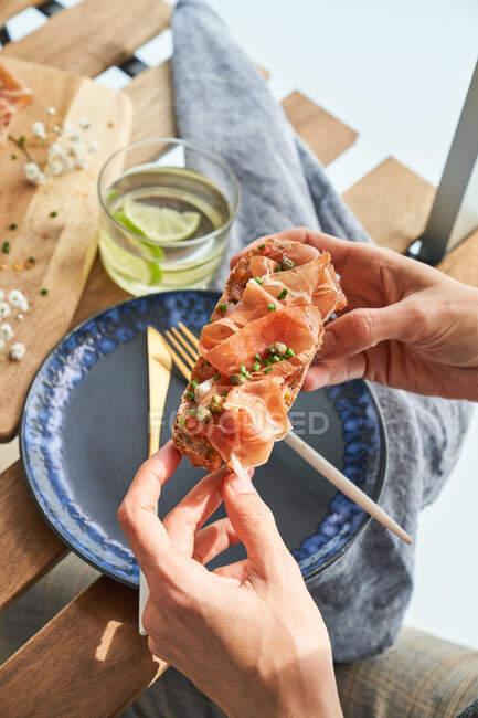 From above of crop hands holding tasty bruschetta with red meat and sauce above table — Stock Photo