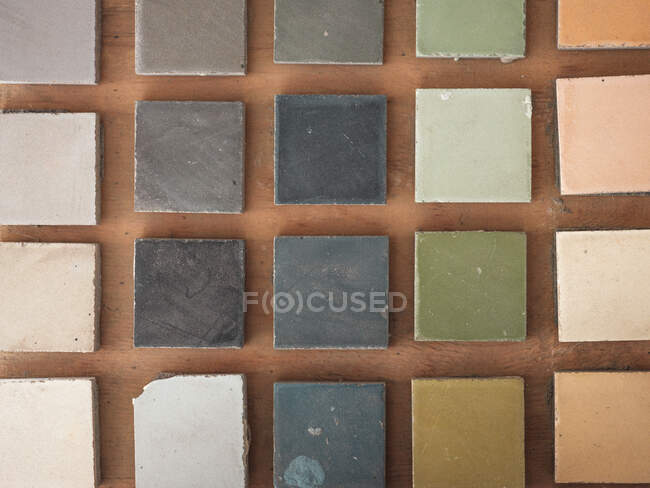 Top view of square samples of handmade tiles pf beautiful cold and warm shades on wooden floor — Stock Photo