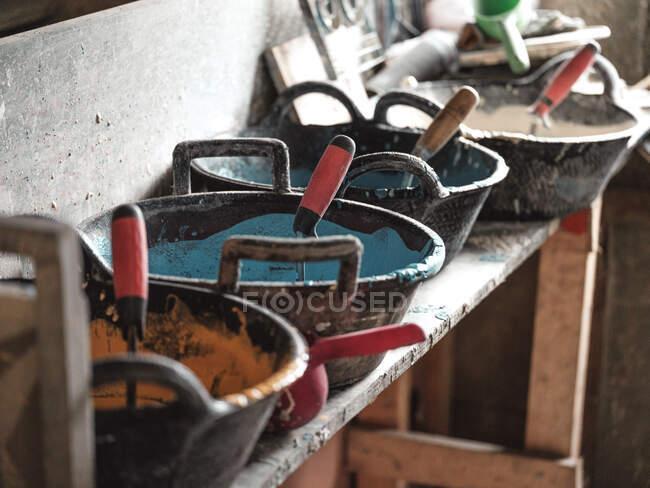 Vista lateral desde arriba de contenedores negros con esmaltes amarillos blancos azules y herramientas en estante de madera en fábrica - foto de stock
