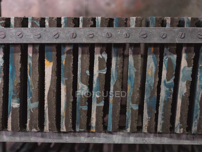 Вид сбоку квадратной плитки с красочными абстрактными орнаментами на металлической полке в мастерской — стоковое фото
