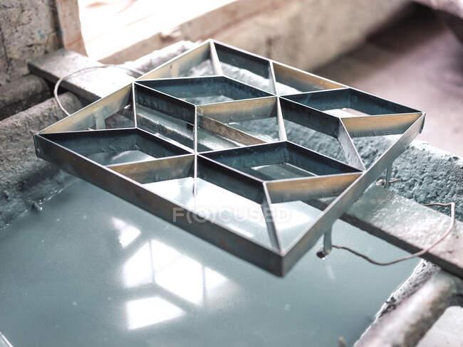 Сверху металлической плитки декоративный трафарет на борту над контейнером с водой с голубой глазурью после мытья — стоковое фото