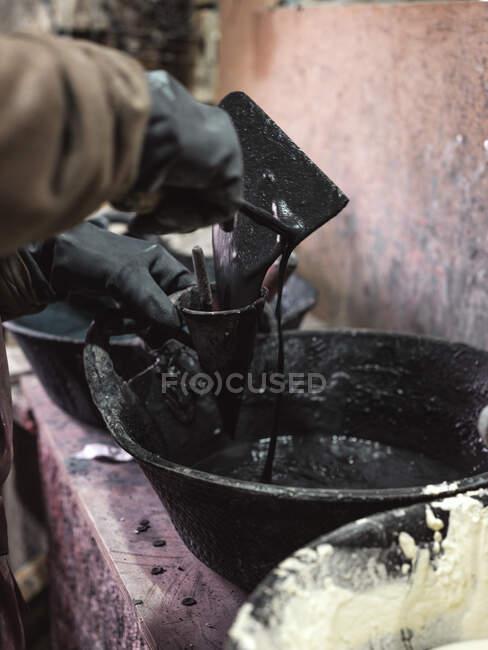 Невпізнаваний працівник врожаю в захисних рукавицях, під час виготовлення плиток у майстерні. — стокове фото