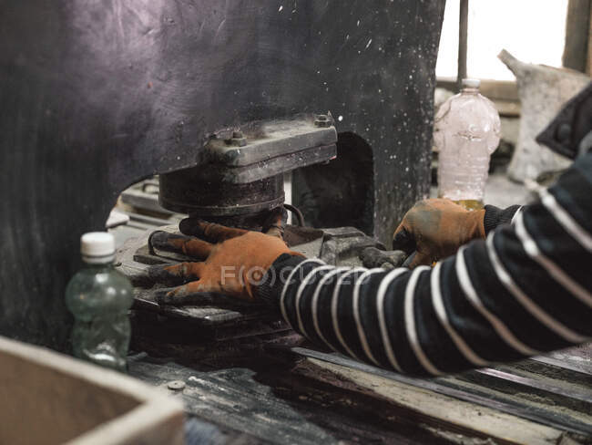 Crop hands in protection gloves of male master setting metal form with material in big metal machine in factory — Stock Photo