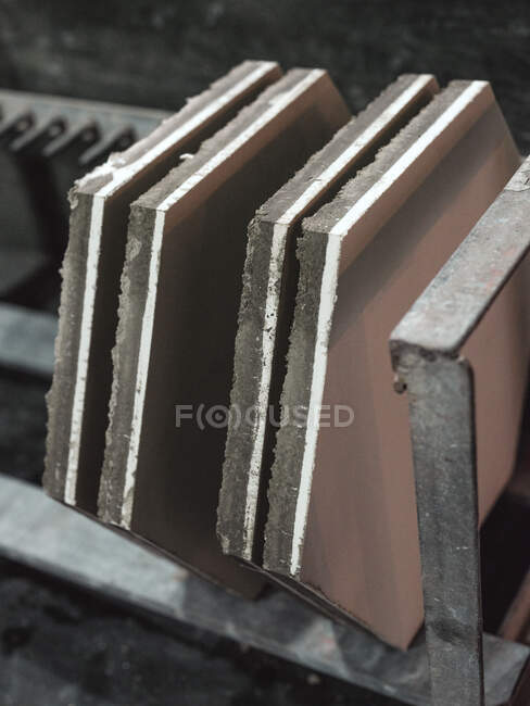 From above of hexagonal big raw ceramic tiles placed on metal shelf in storage of workshop — Stock Photo