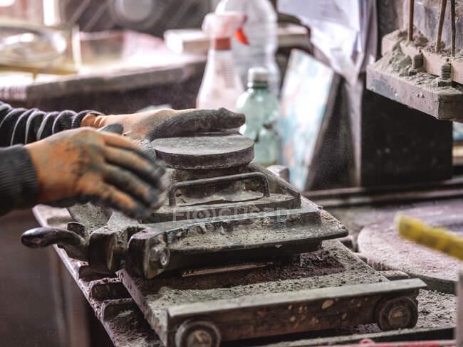 Вигляд збоку зверху на майстра врожаю в рукавицях з використанням металевої машини, а також створення деталей для виробництва на заводі. — стокове фото