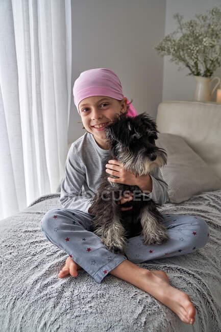 Dall'alto adorabile bambino malato in bandana rosa e pigiama accarezzare animale domestico mentre seduto sul letto a casa a guardare la fotocamera — Foto stock