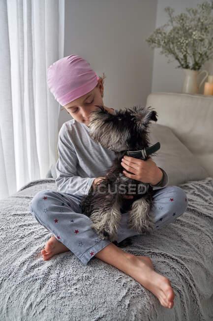 Von oben bezaubernder kranker kleiner Junge in rosa Kopftuch und Pyjama streichelt Haustier, während er zu Hause auf dem Bett sitzt — Stockfoto