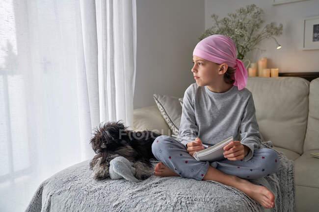 Dal basso bambino felice con malattia del cancro annotazioni di scrittura mentre seduto con cane sul letto in camera — Foto stock