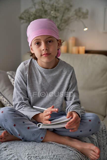 Desde abajo, un niño serio con diagnóstico de cáncer toma notas mientras está sentado en la cama mirando a la cámara - foto de stock