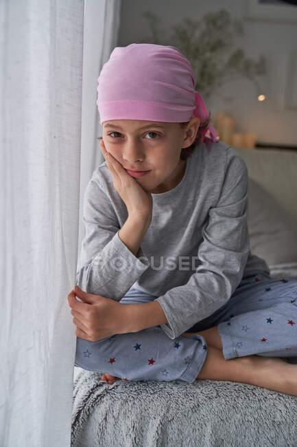 Niño lindo serio en bandana rosa mirando a la cámara y luchando contra el cáncer en casa sentado en un sofá - foto de stock
