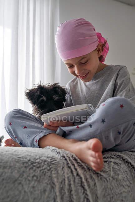 Снизу счастливый маленький ребенок с раковой болезнью пишет заметки, сидя с собакой на кровати в комнате — стоковое фото