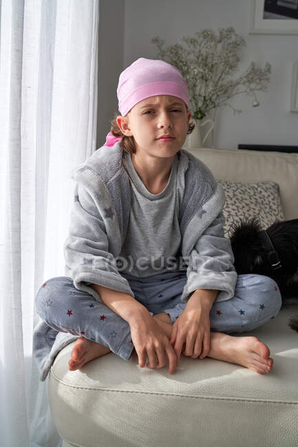Serious cute child in pink bandana looking at camera and fighting cancer at home sitting in a couch — Stock Photo