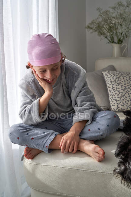 Cheerful cute child in pink bandana looking down and fighting cancer at home sitting in a couch — Stock Photo