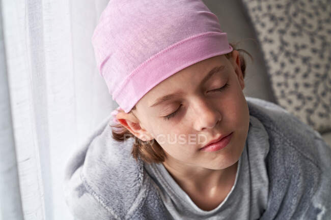 Serious cute child in pink bandana with closed eyes fighting cancer at home sitting in a couch — Stock Photo