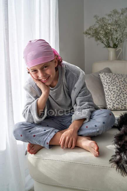 Alegre niño lindo en bandana rosa mirando a la cámara y luchando contra el cáncer en casa sentado en un sofá - foto de stock