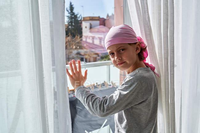 Vista lateral del niño con cáncer usando pañuelo rosa y poniendo las manos en la ventana en la habitación mirando a la cámara - foto de stock