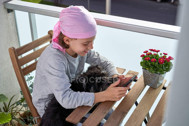 Cheerful little child with cancer disease enjoying pastime with cellphone on terrace while holding a small dog — Stock Photo