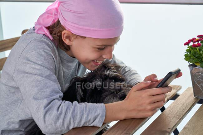Fröhliches kleines krebskrankes Kind genießt Zeitvertreib mit Handy auf der Terrasse, während es einen kleinen Hund hält — Stockfoto