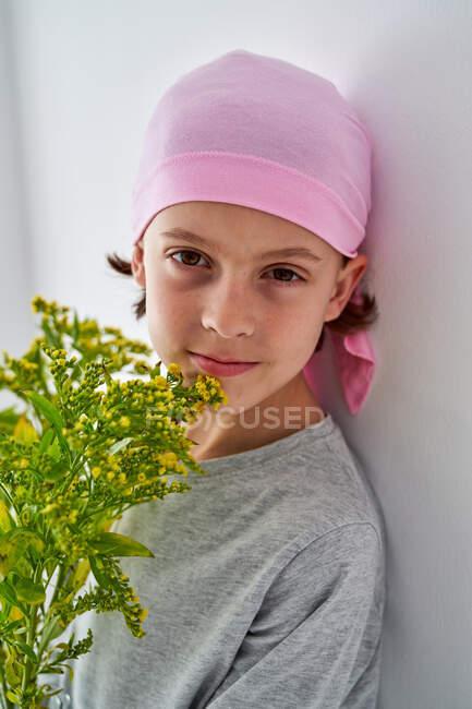 Niño alegre con diagnóstico de cáncer vistiendo pañuelo rosa y mirando a la cámara mientras sostiene el jarrón con flores y de pie en la pared - foto de stock